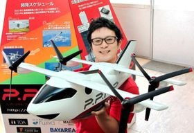 空飛ぶクルマの開発に取り組むスカイリンクテクノロジーズの森本高広社長と、目指す航空機の模型=神戸市西区平野町印路