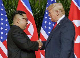 会談の冒頭で握手する北朝鮮の金正恩朝鮮労働党委員長(左)とトランプ米大統領=12日、シンガポール(AP=共同)