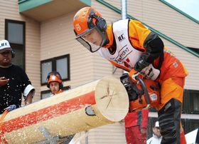 「日本伐木チャンピオンシップ」の決勝戦で丸太を輪切りにする、優勝した先崎倫正さん=20日、青森市