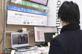 東京・池袋のビックカメラのテレワーク向けコーナーで商品を見る男性