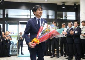 職員に出迎えられて登庁する田上市長=長崎市役所