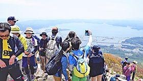 眼下に猪苗代湖を望み、頂上で記念撮影を楽しむ登山者=27日午前
