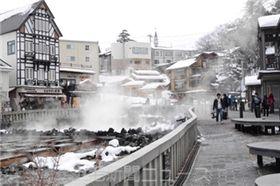 雪化粧した湯畑周辺では普段通りに観光客の姿が見られた=23日