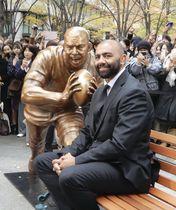 母校に寄贈する自身の像と写真に納まるラグビーW杯日本代表の主将を務めたリーチ・マイケル選手=11日午後、東京・丸の内