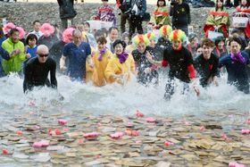 「仙人風呂」に浮かべられた札めがけ、しぶきを上げながら走る参加者=21日、和歌山県田辺市の川湯温泉