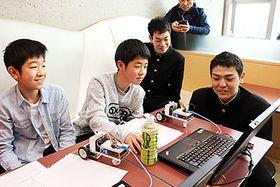 生徒(右)に教わりながらプログラミングに取り組む児童
