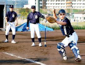 沖監督(中央)の指導の下、初練習に取り組む聖カタリナ大硬式野球部=22日、松山市河野別府