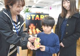 「S―PULSE PHONE」を受け取る男児(中央)=20日午後、静岡市駿河区の@Sストア