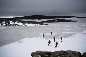 18日、アイスランドで「オク氷河」だった火山に積もった雪の上を歩く人々(AP=共同)