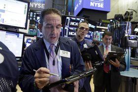 ニューヨーク証券取引所のトレーダーたち=14日(AP=共同)
