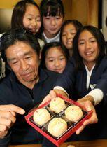 完成した菓子について話す高田社長(左端)と児童