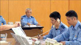 現場に無線で指令を出す警察官=20日午前、松前町西古泉