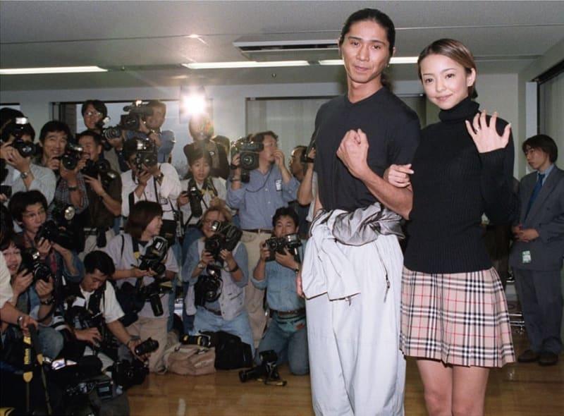 結婚発表の記者会見で、詰め掛けたカメラマンに囲まれ結婚指輪を披露する安室奈美恵さんとSAMさん=1997年10月23日午後、東京都港区南青山