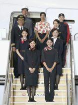 来春から着用する新たな制服を披露する日航の客室乗務員やパイロットら=23日午前、東京都大田区