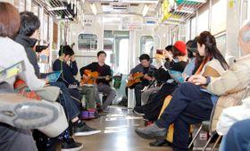 貸し切り電車の車内で音楽を楽しむ来場者ら=高松市屋島中町、琴電屋島駅