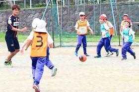 選手と一緒にボールを追い掛ける城山小の子どもたち