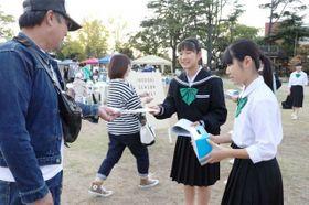 「防災新聞」を手渡す真備中の生徒ら
