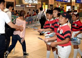 ラグビーワールドカップをPRするチラシを配る子どもたち=26日午前8時半ごろ、福岡市・天神