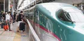 JR東日本のホームから新幹線に乗り込む人たち=7日午後、JR東京駅
