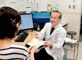 「こんなサイトがありますよ」。四国がんセンターの外来で患者にリーフレットを手渡す主治医(大住省三がん診断・治療開発部長)