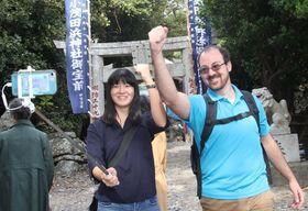 スマートフォンの自撮り機能を使い、対馬のPR動画のオープニング部分を撮影した稲垣さん(左)とメドーズさん=対馬市厳原町、小茂田浜神社