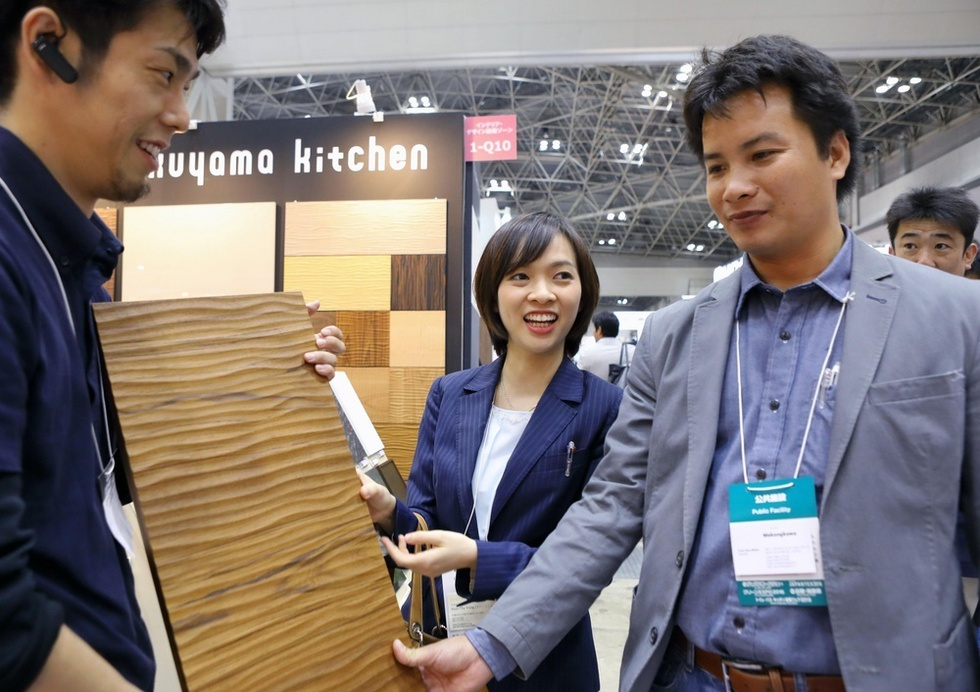 建材関係の展示を見て回るドアン・ティ・チャン(中央)とトラン・フー・ニャン(右)=東京都江東区の東京ビッグサイト