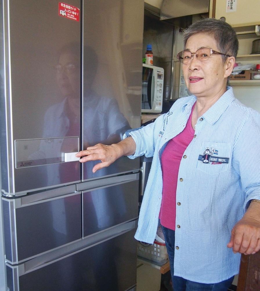 冷蔵庫扉のセンサーに触れる井上恵美子