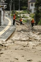 広島県坂町のJR呉線水尻駅で、線路に流入した土砂の様子を調べるJR西日本の職員=12日撮影