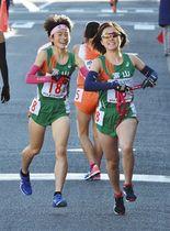 富山アンカーの福居紗希選手(右)へたすきをつなぐ8区の中才茉子選手=京都市内で
