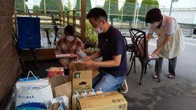 寄付された食品、日用品を確認するフード&ライフドライブのスタッフ=4日、倉敷市水島北幸町の「ひろばにじいろ」