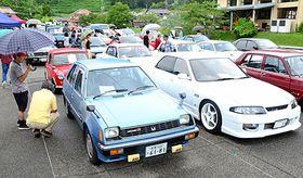 会場に並ぶ旧車に見入る来場者=浜田市弥栄町長安本郷