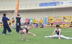 学生が部活動で磨いた技を披露しながら短距離走をする「アスリートダービー」=鹿屋市の鹿屋体育大学