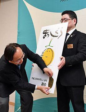 パネルに「まっしぐら」特A取得を祝う金色のシールを貼る三村知事(左)
