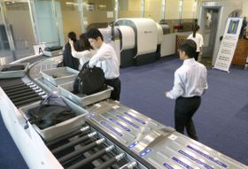 羽田空港で運用が始まったCTと「スマートレーン」を組み合わせた手荷物検査=19日午前