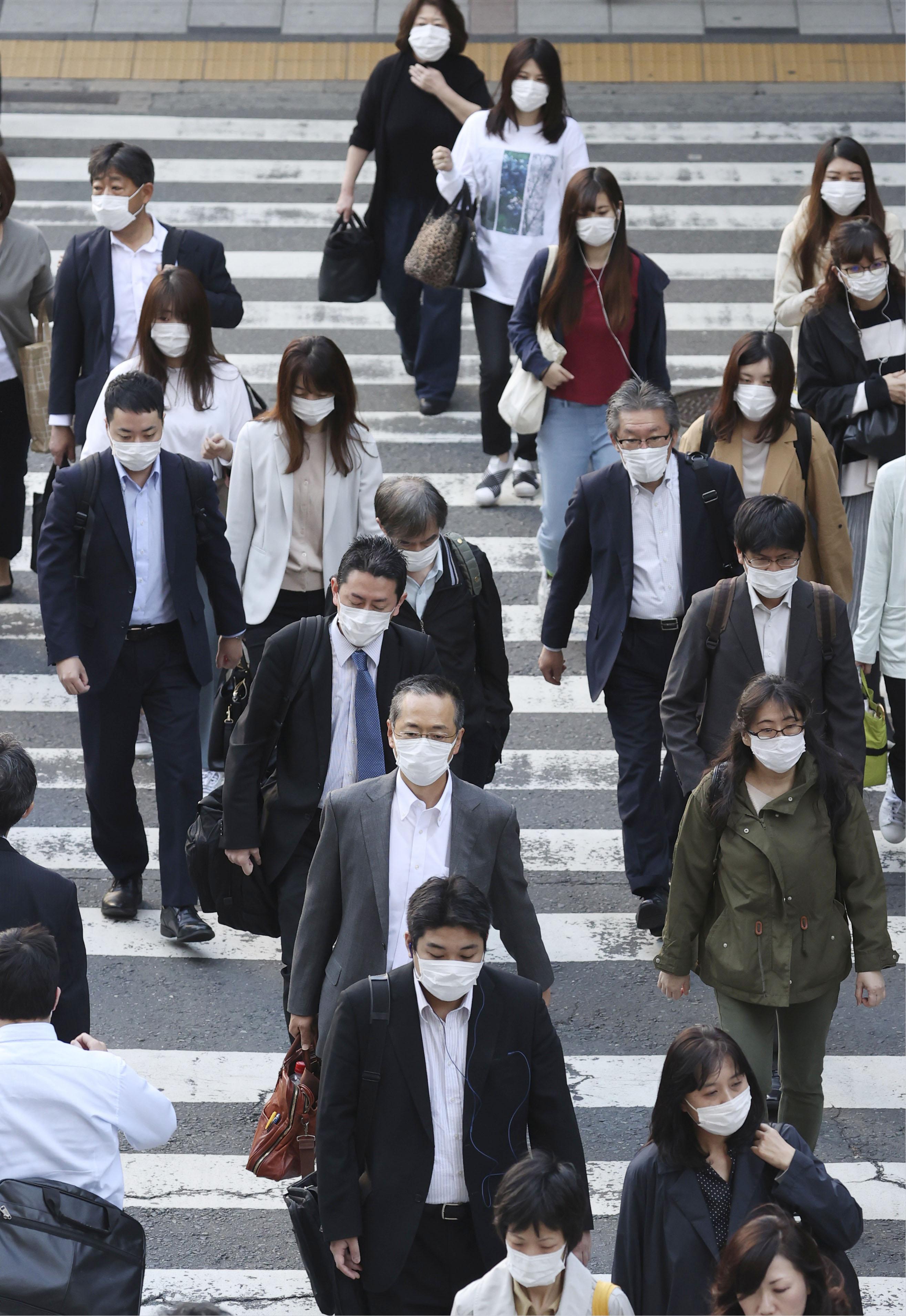 マスク姿で通勤する人たち=7日午前、大阪・梅田