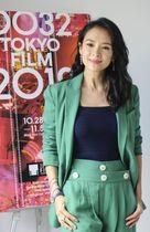 東京国際映画祭のポスターを背に撮影に応じるチャン・ツィイーさん=22日、フランス・カンヌ(共同)