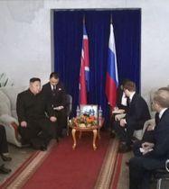 24日、ロシア・ハサン駅に到着し、コズロフ極東・北極圏発展相らの出迎えを受ける北朝鮮の金正恩朝鮮労働党委員長(左)(共同)