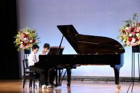 スタインウェイ社製のグランドピアノを弾く参加者