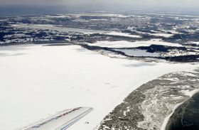 米軍のF16戦闘機が燃料タンクを投棄した小川原湖(手前)。湖面は雪に覆われている。奥は三沢基地=20日午後1時2分、青森県東北町(共同通信社機から)