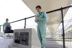 橋桁落下現場の国道176号の脇に設置された石碑の前で、手を合わせる横河ブリッジの有原隆雄常務=22日午前、神戸市