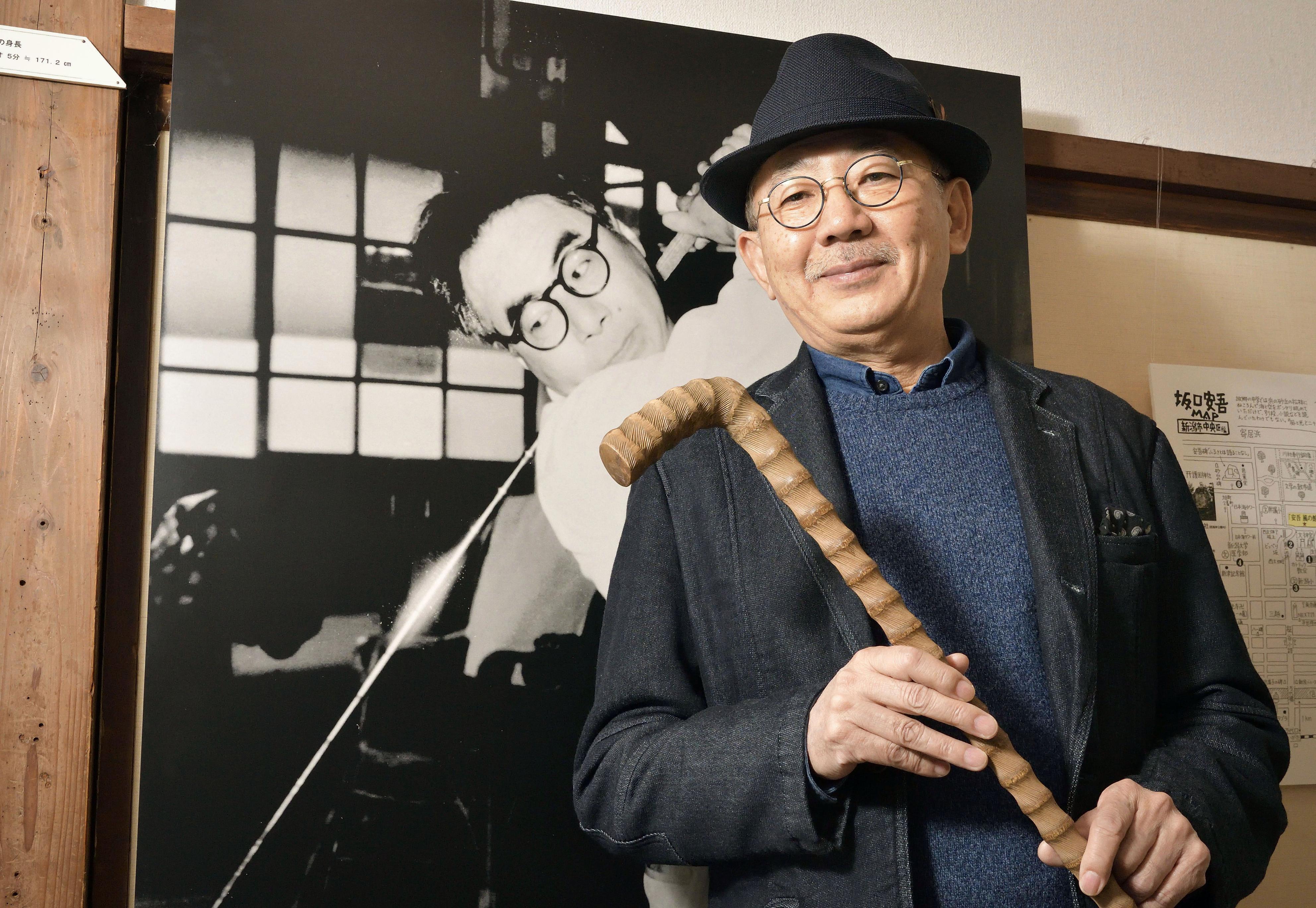 遺品のつえを手に父安吾を語る綱男。「安吾 風の館」にはゴルフクラブを振る坂口安吾の等身大写真が飾られている=新潟市