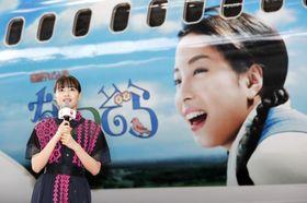 NHK連続テレビ小説「なつぞら」デザインの特別機を背に、あいさつする女優の広瀬すずさん=19日午後、羽田空港