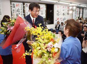 花束を受け取り、再選を喜ぶ三宅氏(左)=21日午後8時36分、高松市