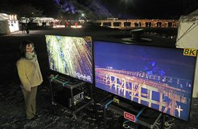 2台の8K対応テレビに映し出された渡月橋のライブ映像と嵯峨野地区の映像(13日午後6時45分、京都市右京区)