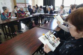 完成した「わたしもじだいのいちぶです」を見る執筆した女性ら=16日、川崎市川崎区
