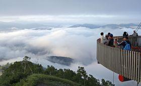 北海道中央部・占冠村の観光施設、星野リゾートトマムで「雲海」を楽しむ観光客ら。雲海は湿度が高く、前日の気温が高く夜冷え込んだ翌朝などに発生しやすい=19日