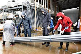 雨の降る中、復旧作業を手伝う野球部員ら