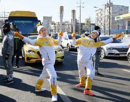 平昌冬季五輪の聖火リレーに参加し、ポーズを決める高橋大輔さん(左)と荒川静香さん=12日、韓国・仁川(共同)