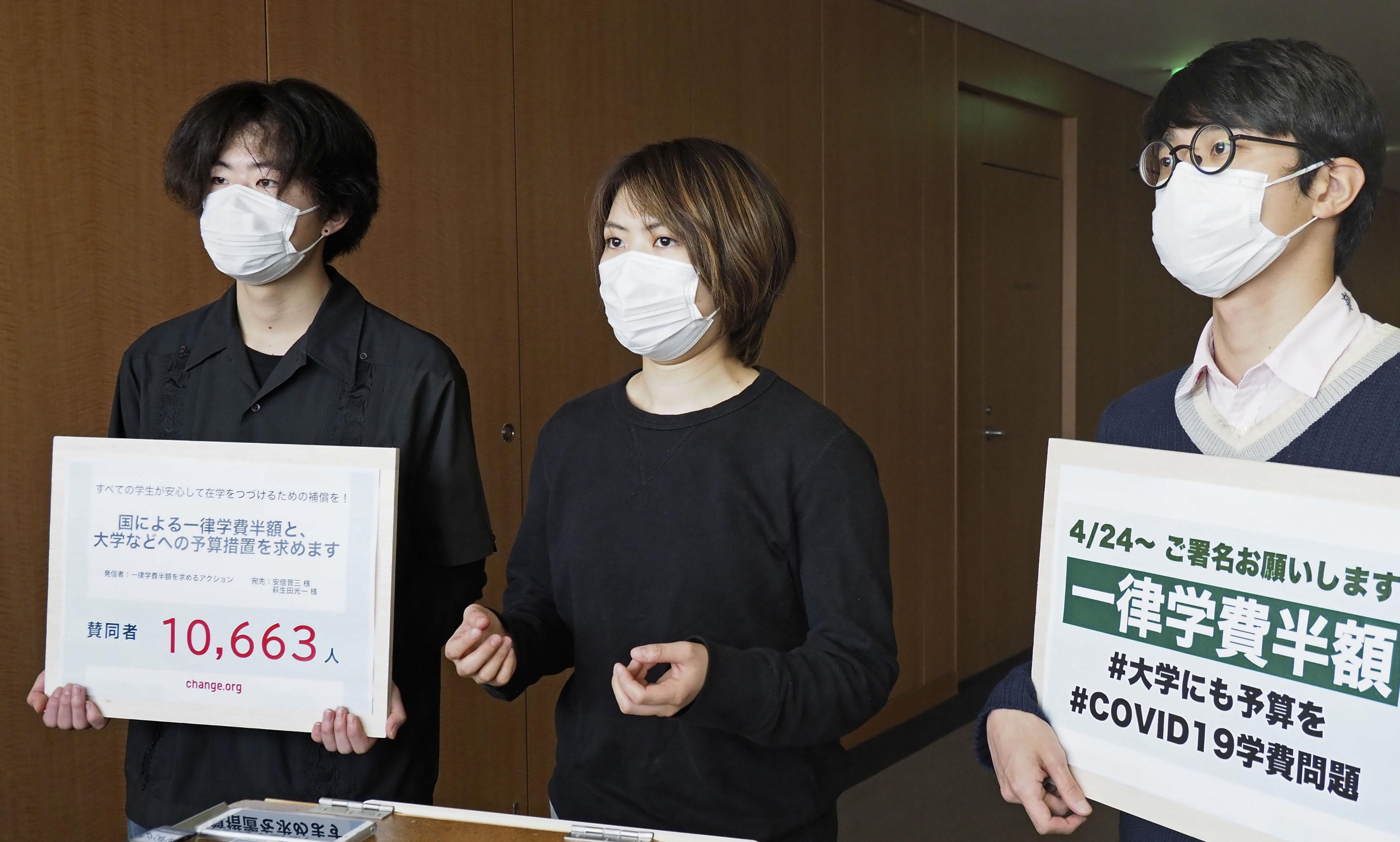 取材に応じる学生団体「一律学費半額を求めるアクション」代表の山岸鞠香さん(中央)ら=30日午後、文科省
