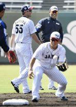 笑顔で練習を見守る稲葉監督(右)。左は秋山=宮崎市